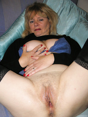 Older blond widens her legs to show moist slit