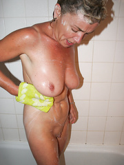 Mature woman nude in shower showing off plump pussy and shaving