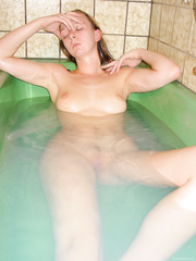 Slim young girlfriend with a lovely figure bathing and posing