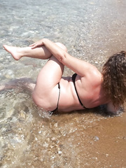 Sexy milf wife frolicking in the beach surf wearing only a bikini