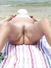 MILF naked on the beach in summer holiday enjoying the sunshine