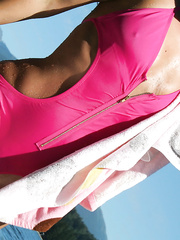 Wearing a bright pink bathing suit breasts and pubic hair visible