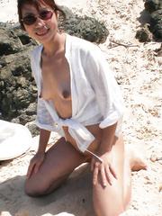 Sexy Asian MILF on Beach feeling sand on smooth skin