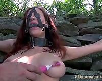Crucified wench with a toy in her cunt suffers outdoors