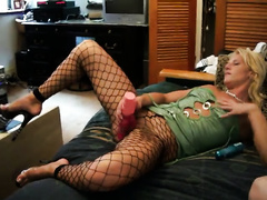Vile blonde whore in fishnet hose is masturbating with large sextoy