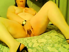 My plump slutty wife wearing high heels fingers her crotch in the bedroom