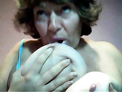 Filthy Granny floozy is engulfing her saggy breasts on cam
