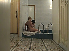 Two lesbos have a fun caressing every other in a sauna in voyeur scene