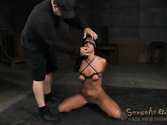 Blindfolded hard bound tanned dark brown stands on knees and gives BJ