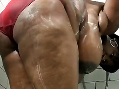 Black big beautiful woman mommy with massive melons is soaping her balloons in the bath