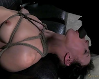 Lying on the dark leather bed fastened up brunette hair sucks master's tool