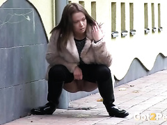 Brunette in fur jacket and dark pants plan to pee right outdoors