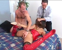 Leggy Asian wench in red latex sex costume sucks 2 white dongs at one time