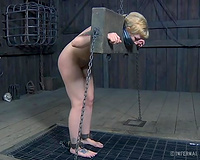 Submissive pale golden-haired with large a-hole is locked in wooden stocks