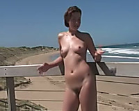 Dainty amateur wife oils up her taut body on the lonely beach