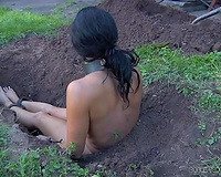 Brunette leashed milf wench buried in the ground outdoors