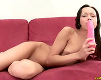 Young lustful slut tickles her wet crack on the couch with sex toy