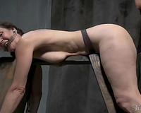 Pale skin milf woman tied to the wooden barrier and gagged