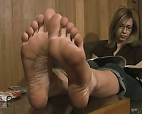 Lovely nerdy girl reads magazine flaunting her soft immodest soles
