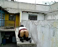 Dirty lady-boy in nylons and small belts masturbates on a roof