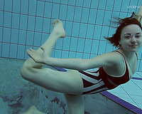 Curvy pale skin redhead chick in the water swims undressed