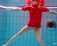 Slender and cute redhead white wife dives in the pool and disrobes underwater