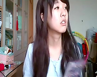 Long-haired Asian sweetheart flashes her pants for the web camera