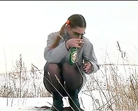 Cute youthful white honey pissing outside in a snowy day