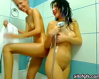 Two charming women are washing every others twats in a shower