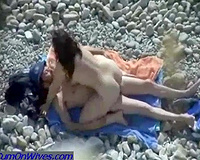 Naughty white milf rides her partner on the exposed beach