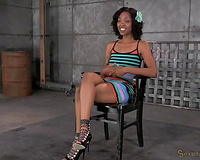 Playful and happy dark housewife gagged and chained on the wooden box