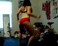 Brunette playgirl wearing pants dances in front of a livecam