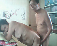 Mature Asian married pair copulates doggy style in the kitchen on web camera