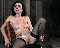 Slender pale and tattooed dark brown rides sex machine during the time that being bound