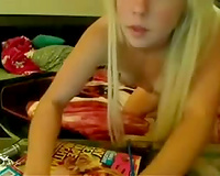 Flamboyant blond lassie plays with her toys on livecam