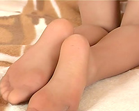 Stunning svelte Asian dark brown legal age teenager disrobes and bows over on the sofa
