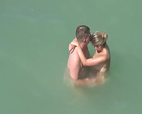 Horny pair having sex in the water on a nudist beach
