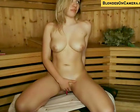 Busty golden-haired cam performer is playing with her sex toys in the sauna