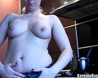 Busty golden-haired Russian woman in the kitchen flashing her goodies