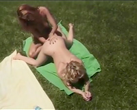 Gorgeous redhead and blonde lesbians make out on the lawn