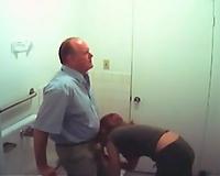 Redhead secretary engulfing boss's jock in a crap-house
