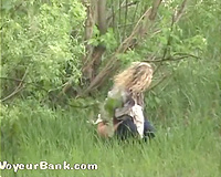 Blonde young white playgirl in the forests squats and voids urine behind the bushes