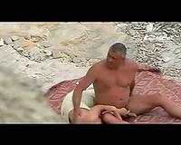 Amateur tugjob on a public nudist beach