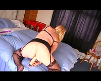 Horny woman in stocking suspenders and brassiere masturbating with sex tool