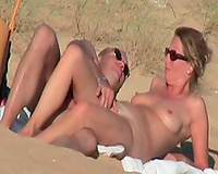A fine aged pair on the nudist beach playing with each other