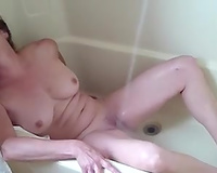 Mature and busty housewife in the bathroom tub masturbating on livecam