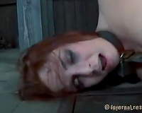 Attractive redhead wench bounded with metallic device is punishment