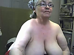Blonde granny plays with her natural jugs in front of a web camera