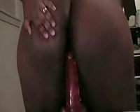 Ebony hottie enjoys playing with a large sex toy in front of a webcam