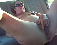 My chunky old dirty slut wife entertains herself by fingering her vagina in a car